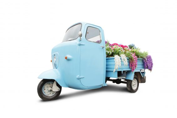 Vintage motorbike with flowers in trunk isolated on white.