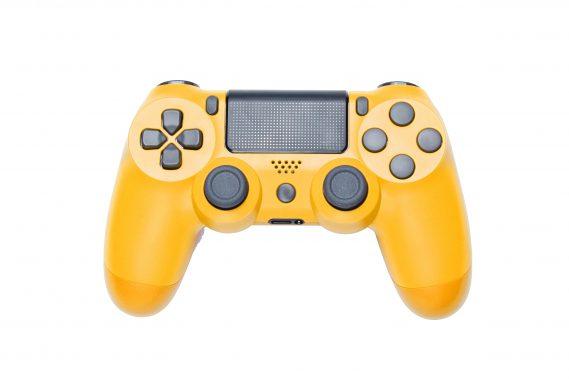 Modern yellow gamepad (joystick) on gray background. Top view